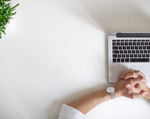 person wearing watch near laptop