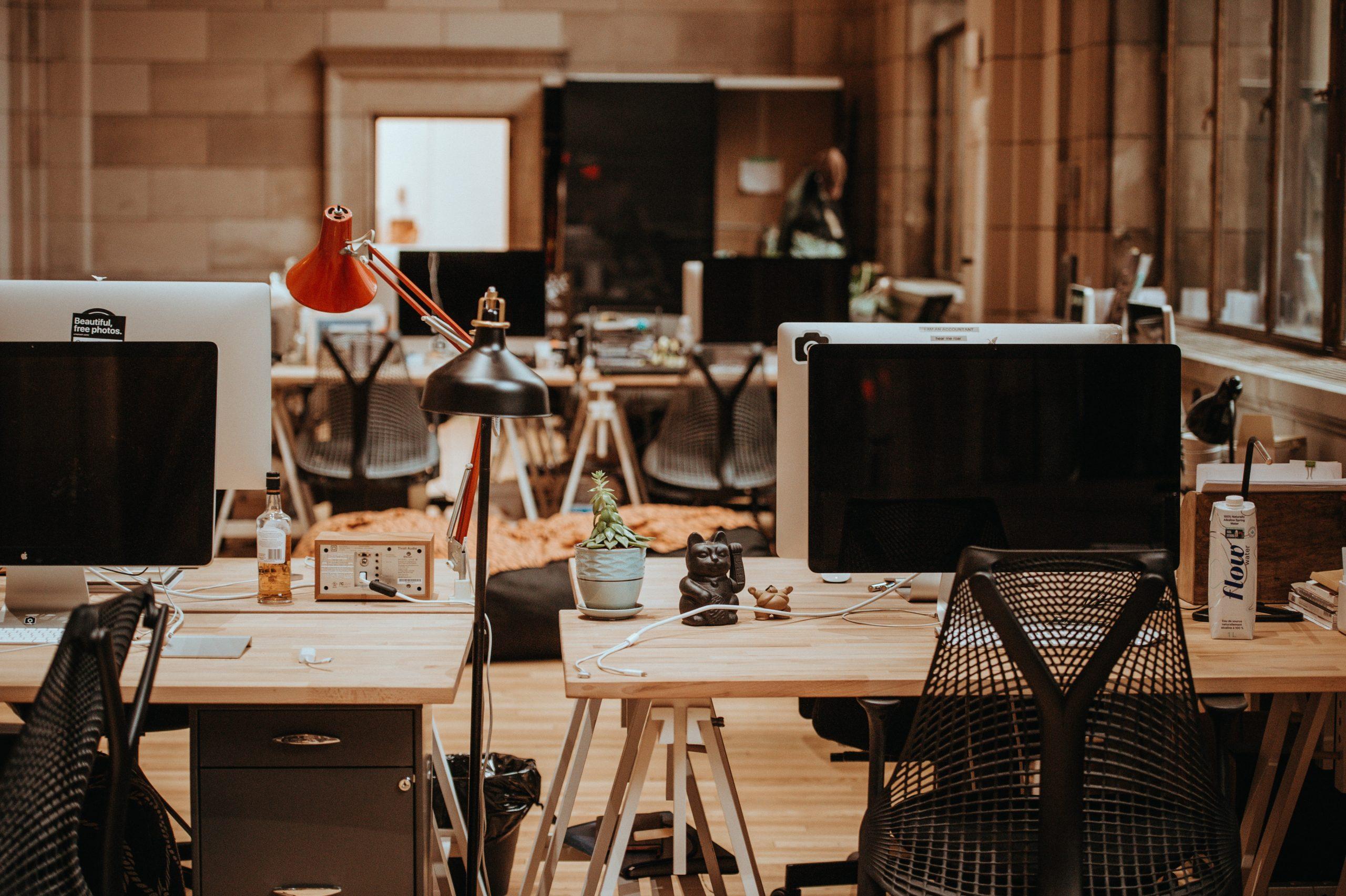 turned off flat screen monitors on top of beige desks