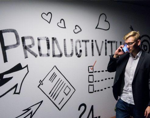 man holding smartphone looking at productivity wall decor