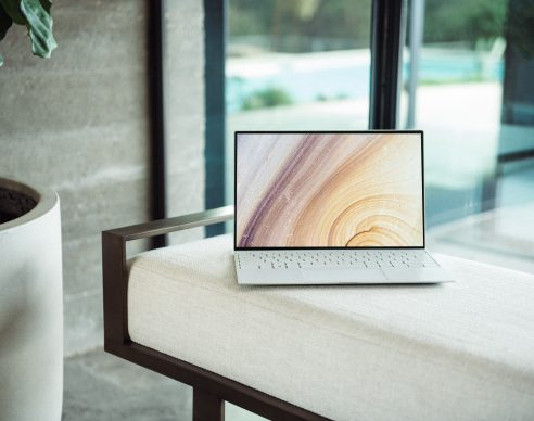 silver macbook on brown wooden table