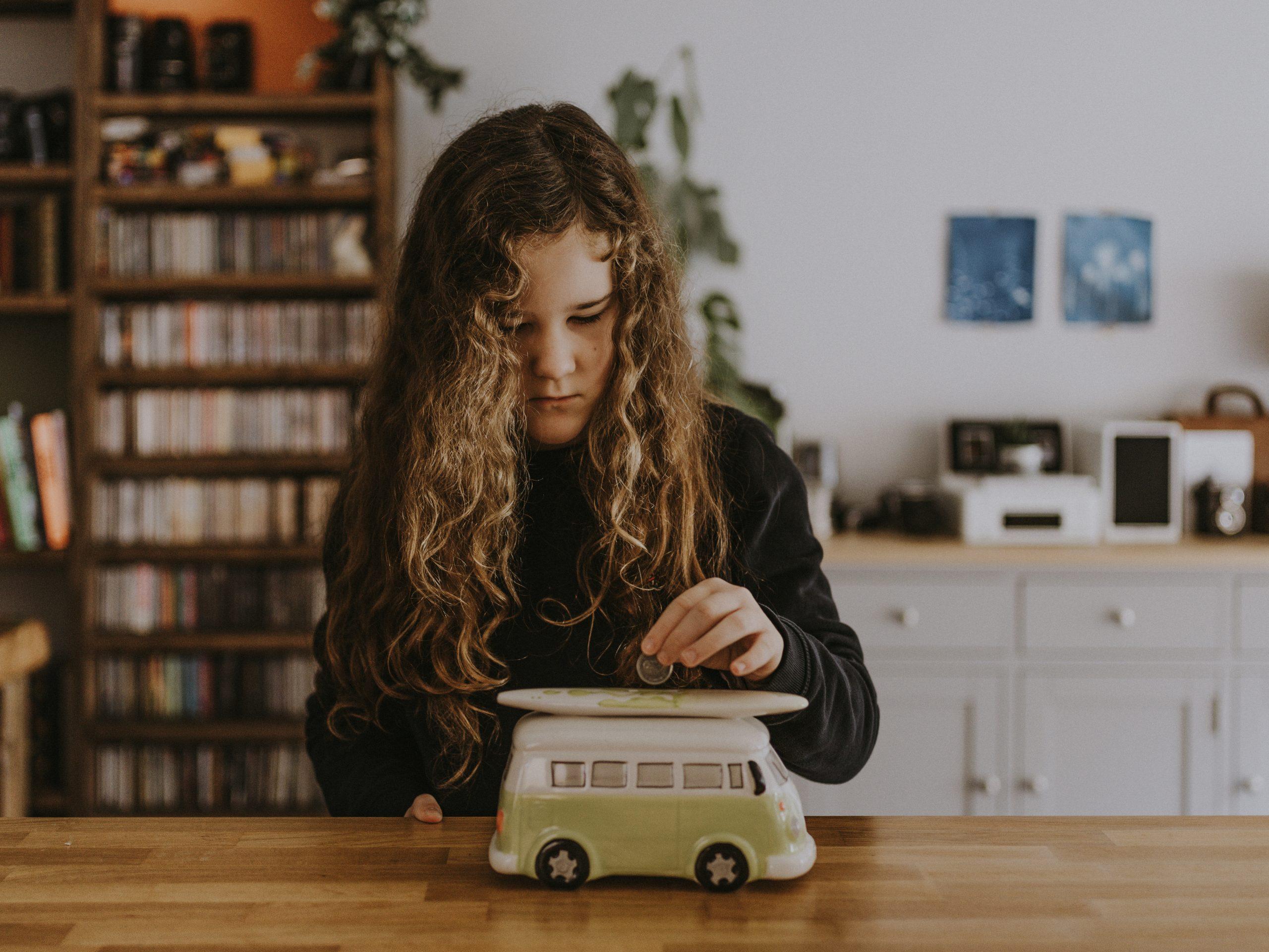 girl wearing black sweatshirt playing toy car