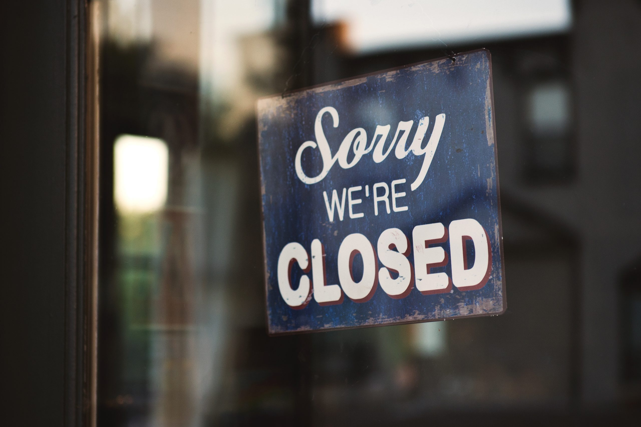 Sorry we're closed signage hanged on glass door